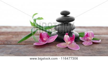 Spa stones with bamboo and purple orchids on white background