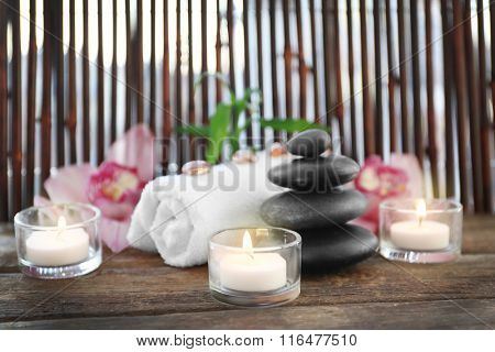 Spa stones with towel, candles, bamboo and pink orchids on wooden background