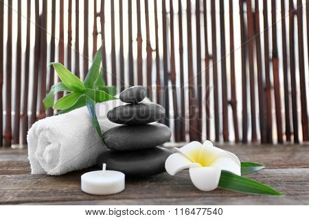 Spa stones with towel, bamboo, candle and tropical flower on wooden background