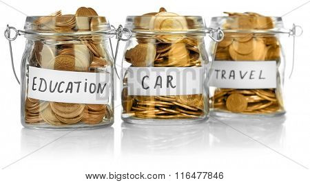Glass jars with Ukrainian coins for car, education and travel, isolated on white