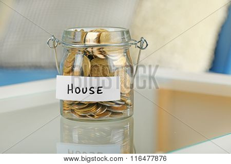 Glass jars with Ukrainian coins for house on a table