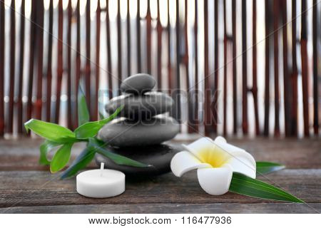 Spa stones with bamboo, candle and tropical flower on wooden background