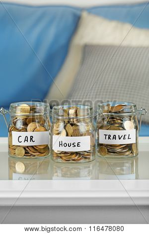 Glass jars with Ukrainian coins for car, house and travel on a table