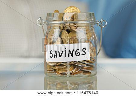 Glass jar with Ukrainian coins for savings on a table