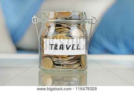 Glass jar with Ukrainian coins for travel on a table