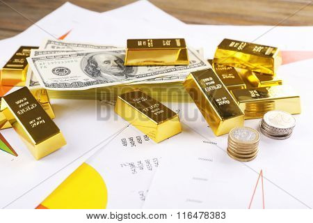 Gold bars with euro coins on paper background