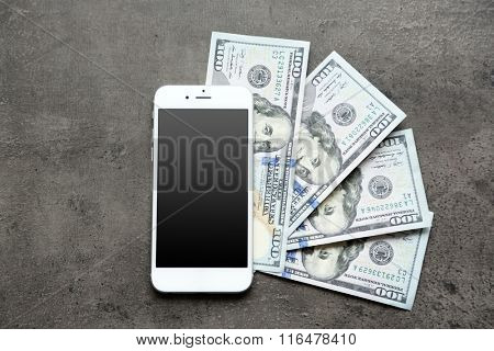 Smart phone with dollar banknotes on grey background. Making money online