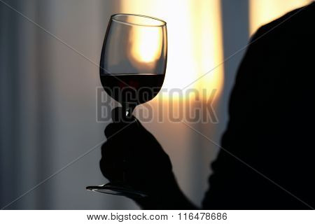 Silhouette of man holding red wine in a glass, close up