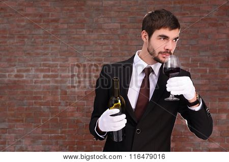Man holding a bottle and sniffing red wine in glass on brick wall background