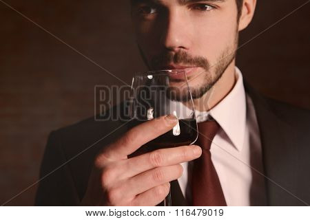 Man sniffing red wine in glass