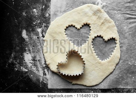 Uncooked heart shaped biscuits on a table