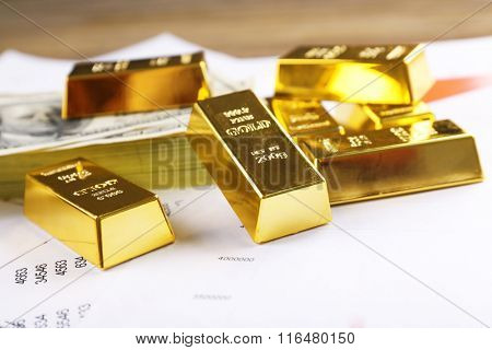 Gold bars with dollar banknotes on paper background, close up
