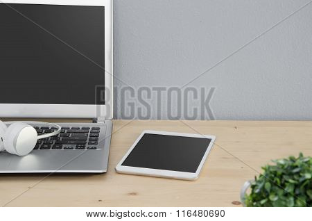 Office Desk With Notebook, Tablet And Earphone.
