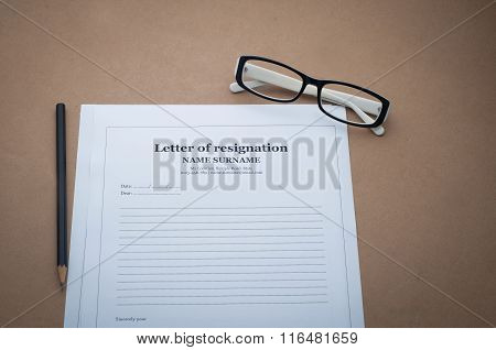 Office Desk With Letter Of Resignation Form And Glasses.