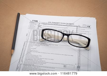 Office Desk With Us Tax Information, Glasses And Black Pencil.