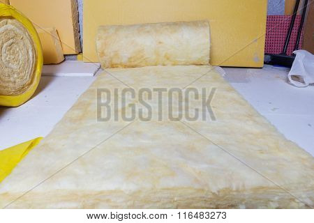 Rolled Out Thermal Insulation Role In Yellow Package At Attic Background