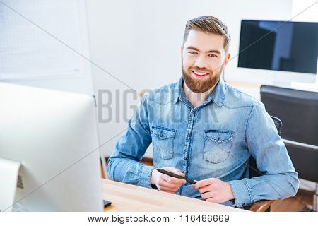 Cheerful handsome young designer with beard in blue shirt holding stylus and sitting at the table in office