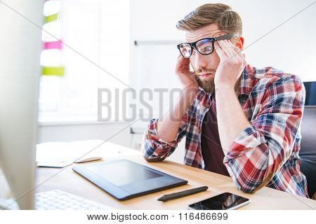 Tired exhausted young man with beard in glasses sitting on workplace and touching temples