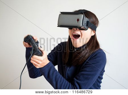 Excited woman play with video game with joystick and virtual reality glasses
