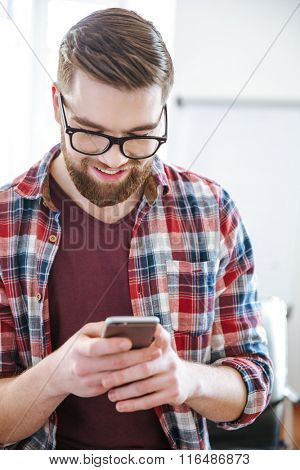 Closeup of smiling handsome bearded man in checkered shirt using mobile phone