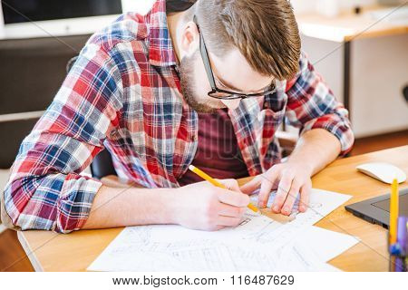 Serious hardworking student with beard in glasses sitting at the desk and drawing blueprint
