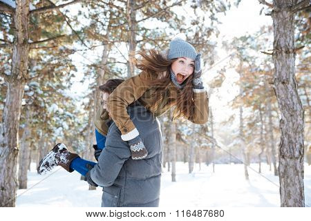 Man carrying cheerful woman on his shoulders in winter park