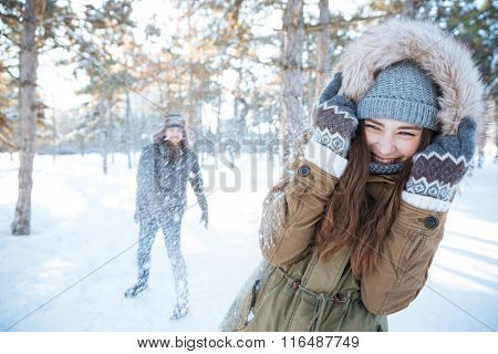 Happy young couple in winter clothes playing snowballs outdoors