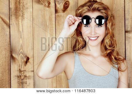 Portrait of a happy young woman with beautiful smile posing by a wooden wall in casual clothes and sunglasses.