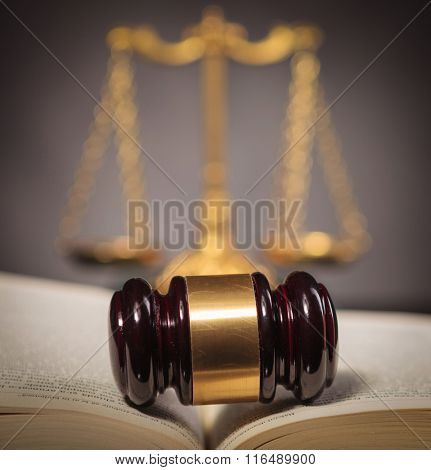 judge's hammer in the middle of a law book in front of a golden scale , fair law and justice concept
