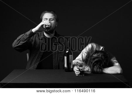 Drunk Woman Is Sleeping On The Table, Her Husband  Is Steel  Keeping  A Glass