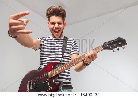 young man screaming and showing the rock and roll sign while playing guitar and looking down at the camera