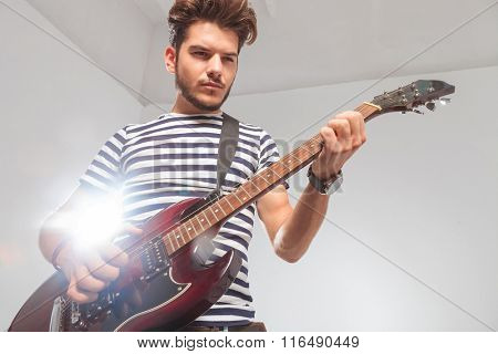 portrait of young rocker pose looking down while playing the electric guitar with light from behind