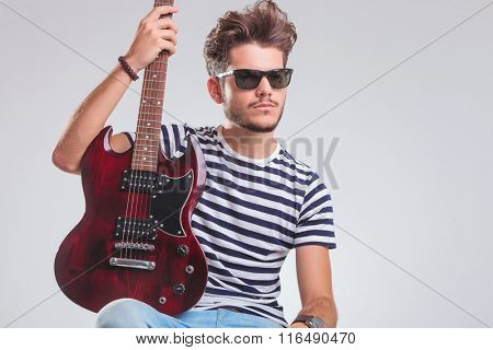 young artist pose seated in studio background with electric guitar in his lap. he is wearing sunglasses while looking away.