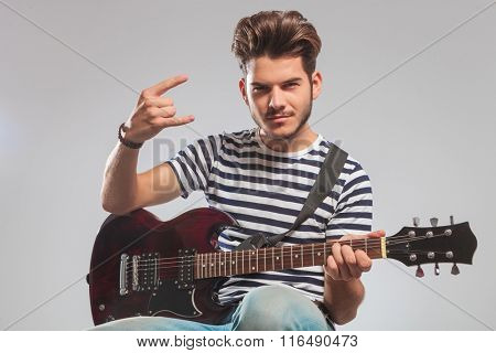 smiling guitarist seated in studio background with guitar on lap while showing rock and roll sign