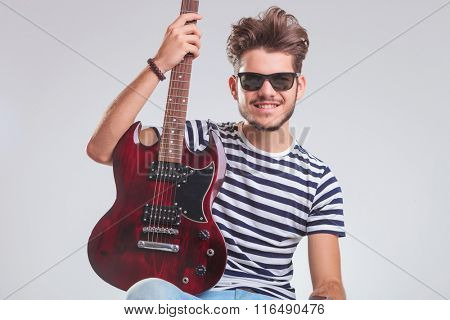 young rocker posing in studio background with electric guitar in his lap. he is seated, wearing sunglasses and is looking at the camera.