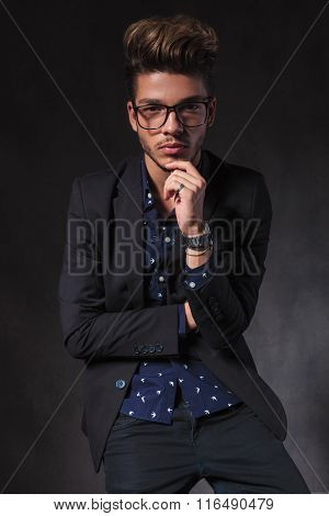 intelligent skinny guy wearing glasses pose seated thinking while looking at the camera in dark studio background