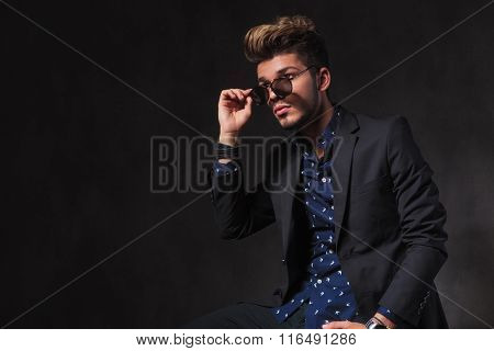 side portrait of fashionable young man posing in dark studio background while seated. he is taking off his sunglasses.