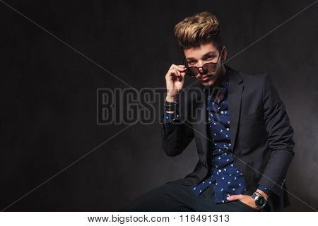 portrait of seated handsome man in dark studio background. he is taking off his sunglasses while having a hand in pocket.