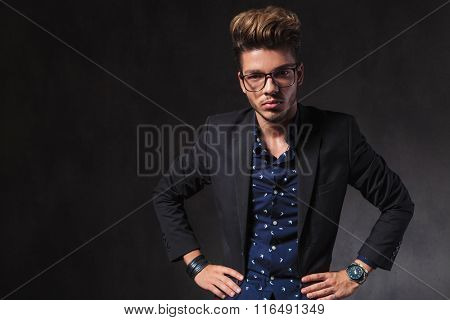 inteligent handsome man wearing glasses pose in dark studio background starring at the camera with hands on waist