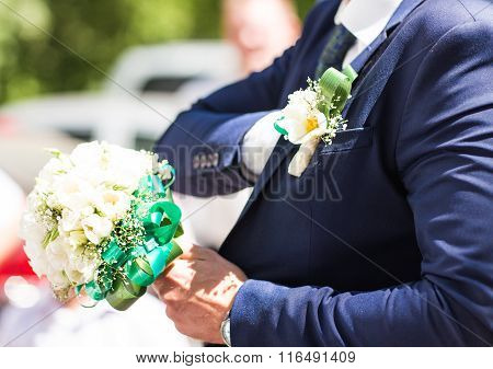Beautiful wedding bouquet in hands of the groom. Gift to the bride.Blue classic designer suit with