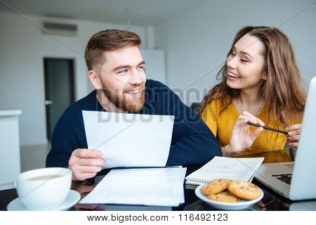 Portrait of a cheerful young couple calculating their bills at home