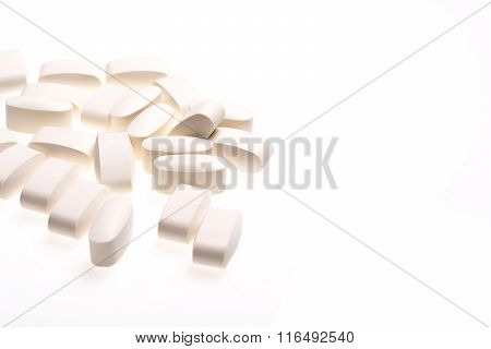 White medical pills for treating diseases on a white background