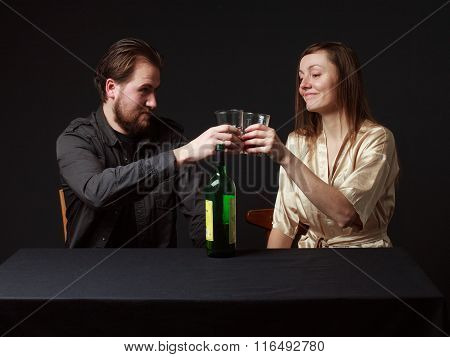Alcoholism. Man And Woman Are Boozing, Bottle On The Table, Smiling