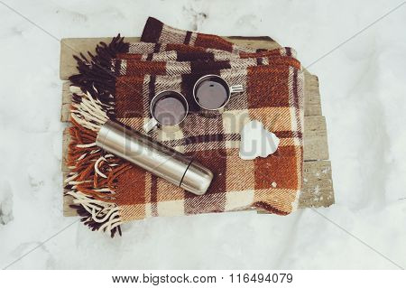winter picnic on the snow. Hot tea thermos and snowball heart on cozy warm blanket. Outdoor seasonal