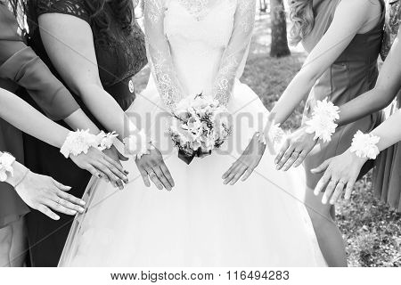 The bride and bridesmaids are showing beautiful flowers on their hands.