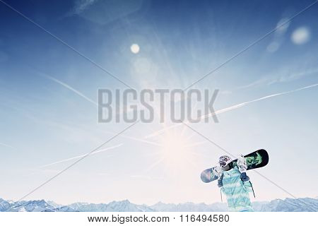 Female snowboarder wearing colorful helmet, blue jacket and grey gloves standing with snowboard in her hands and preparing for ride - snowboarding concept
