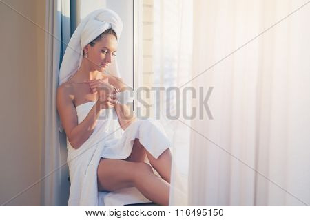 Romantic woman sitting before window and admiring sunrise or sunset with towel on her head body afte