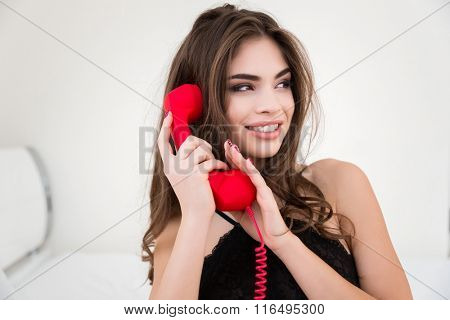 Portrait of a happy woman covering microphone on the red phone tube and looking away