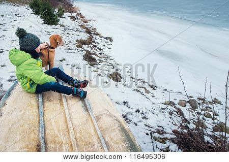 Boy With Dog Sitting Together Near Frozen Lake