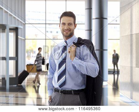 Portrait of happy elegant businessman in office lobby.